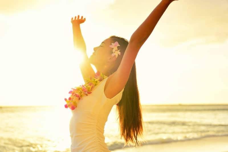 Femme à Hawaii écartant ses bras sur un couché de soleil