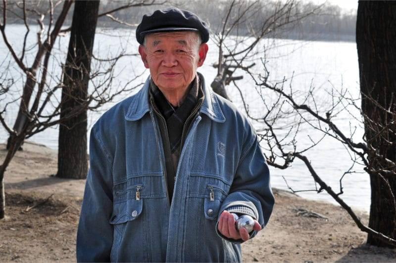 Chinois agé tenant des boules Qi Gong