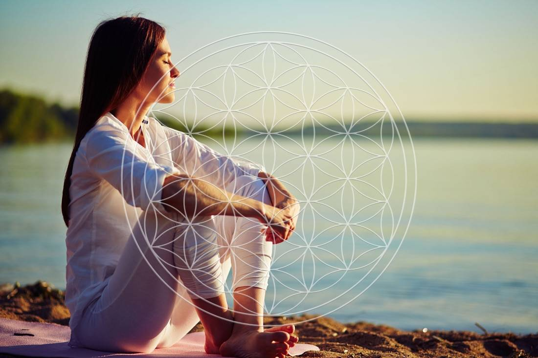 Femme se retrouvant proche de la mer avec le symbole de la fleur de vie