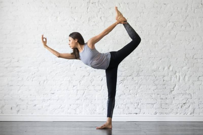 Jeune femme pratiquant la posture du danceur