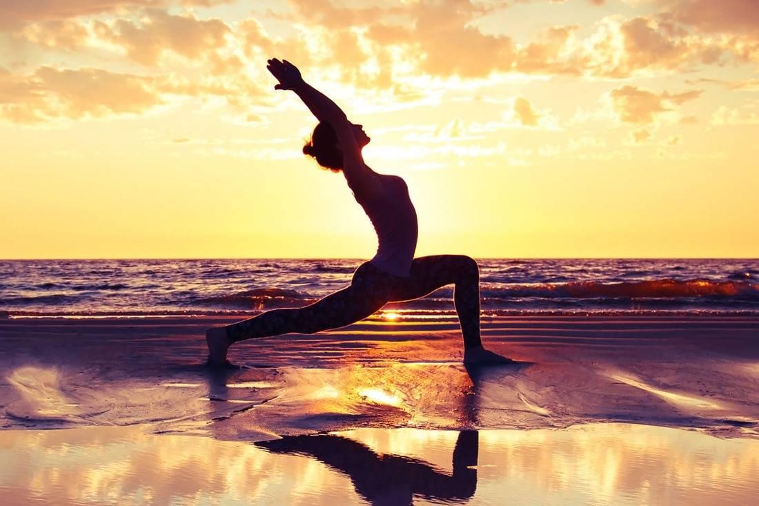 Jeune femme sur la plage pratiquant le yoga