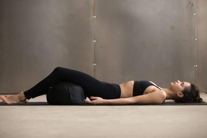Femme allongée avec un zafu noir
