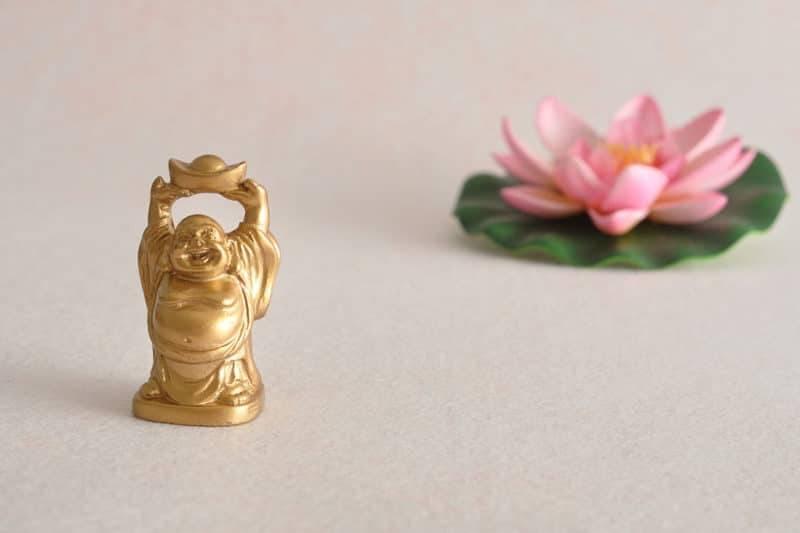 Statuette d'un bouddha rieur en or avec un bol au dessus de sa tête