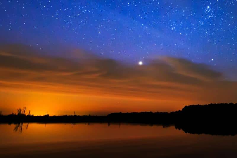 Un matin à l'aube sur un ciel étoilé de fond reflète dans l'eau du lac.