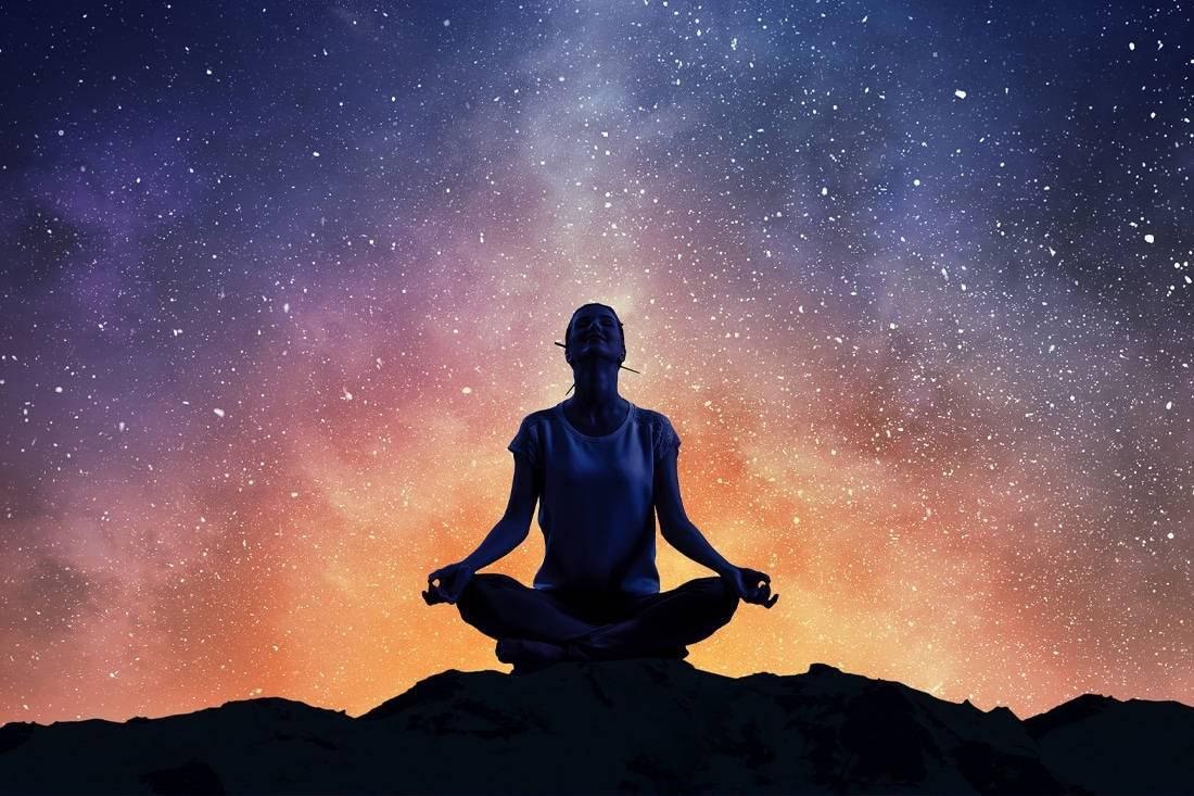 Jeune femme qui médite sous les étoiles