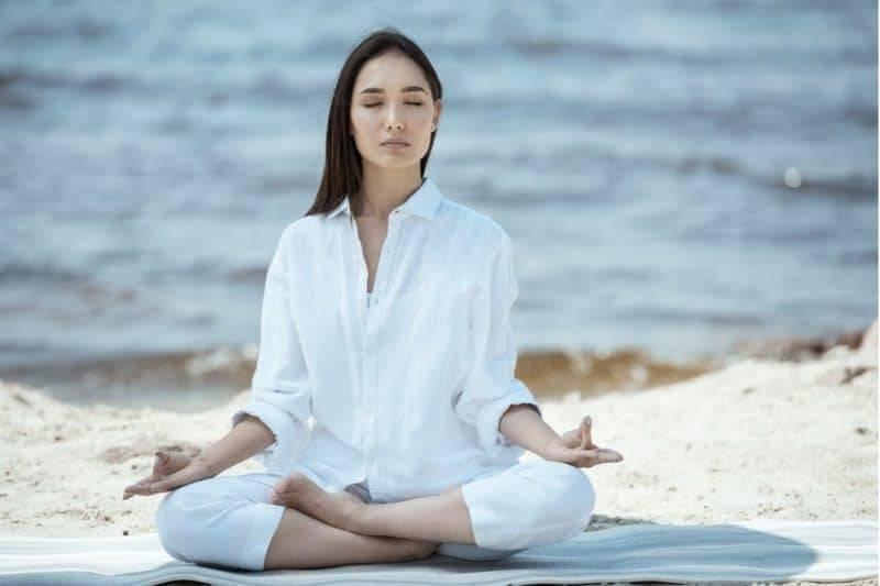 Femme méditant sur la plage.